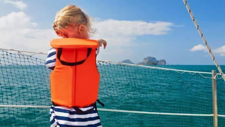 Kind in Schwimmweste auf Boot