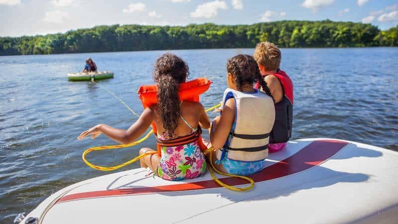 Kinder im Wasser auf Boot und Reifen