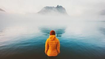 Frau in orange Outdoorjacke vor See